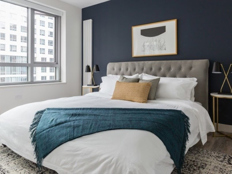 A focused look at this master bedroom's large modern bed with stylish table lamps on both sides. The room features a white and dark gray walls, along with glass windows.