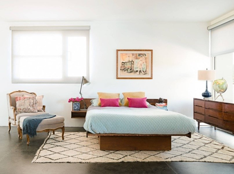 Primary bedroom featuring a cozy bed with built-in side tables. The room offers white walls and ceiling, along with hardwood flooring.
