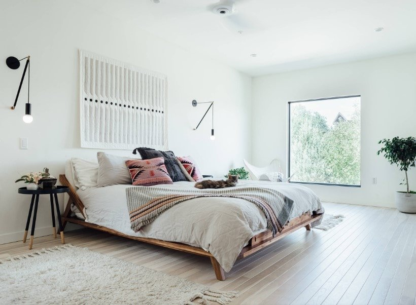 A spacious Eclectic master bedroom featuring white walls and a white ceiling, together with hardwood flooring. The room offers a large bed setup lighted by stylish wall lights.