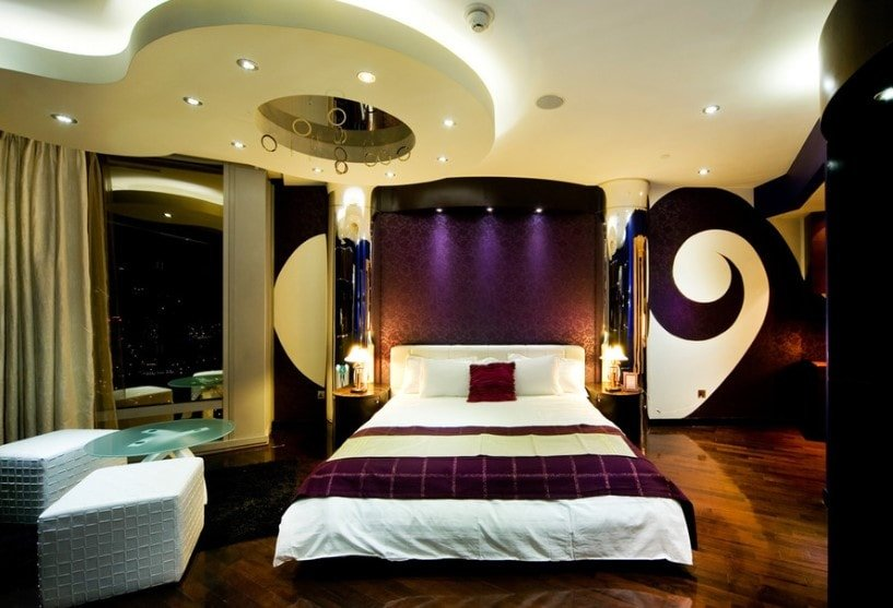 A glamorous primary bedroom boasting a stunning custom ceiling and stylish wall designs, along with hardwood flooring and glass windows. The room offers a luxurious bed setup along with a pair of white seats on the side with a glass center table.