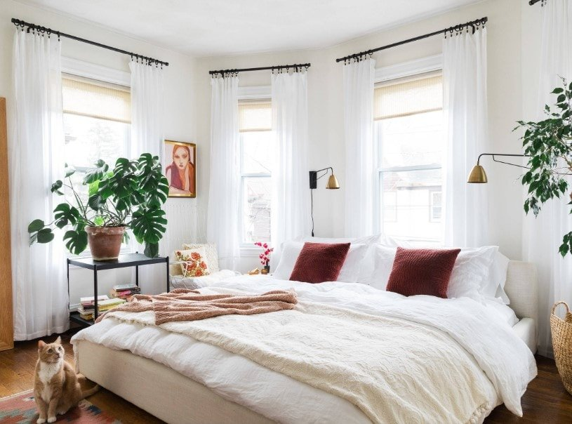 A focused shot at this master bedroom's large comfy bed surrounded by white walls and lovely white window curtains.