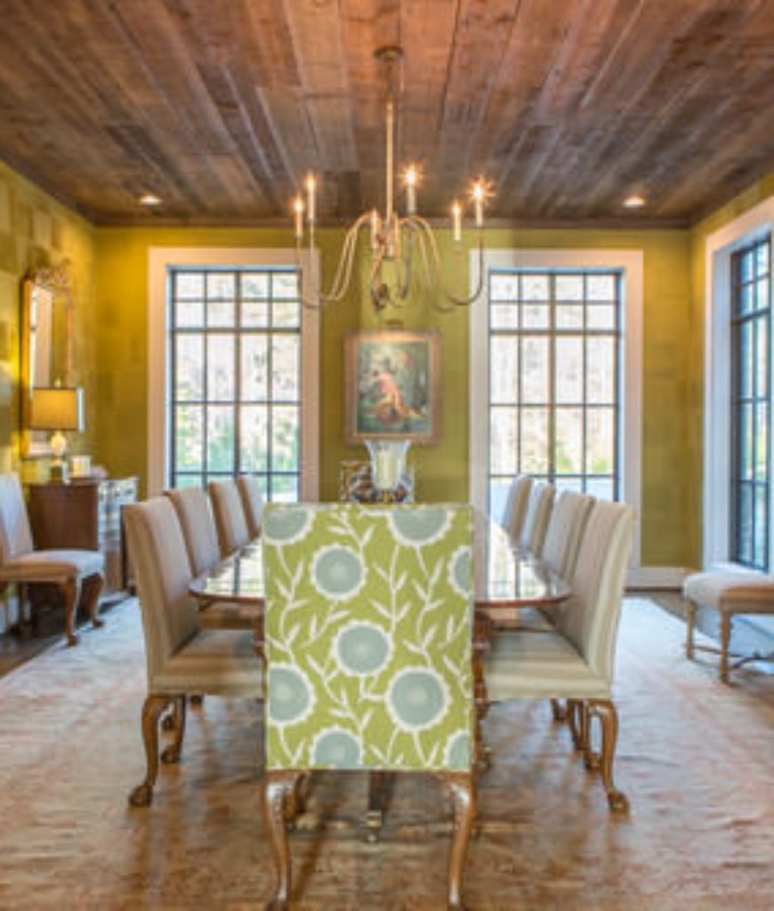 Green farmhouse dining room with carpeted hardwood floor and chandelier.