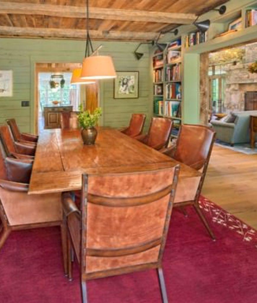 Rustic green dining room with hardwood floor, built-in bookshelf, and pendant light.