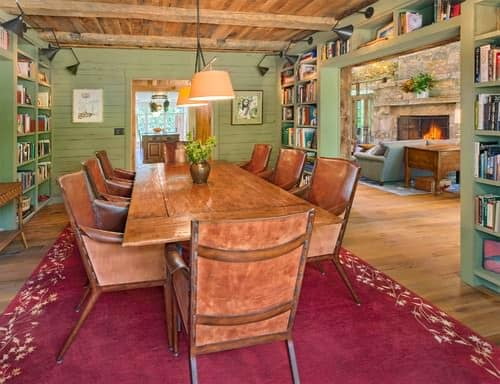 Rustic green dining room with hardwood floor, built-in bookshelf, and pendant light.