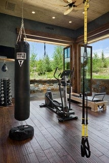 Rustic home gym with hardwood flooring and ceiling fan.