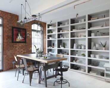 Industrial dining room with built-in shelving, vintage industrial pendant lights, exposed brick accent wall and a dining table set of vintage old factory pieces.