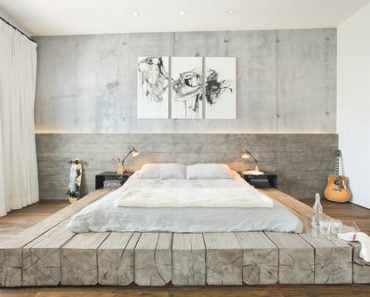 Industrial master bedroom with grey walls and wooden bed base.
