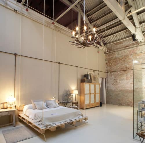 Industrial master bedroom with chandelier and ceiling with beams.
