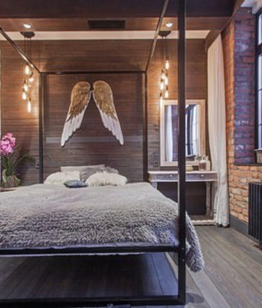 Industrial master bedroom with pendant light and hardwood floor.