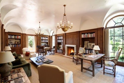 Mediterranean home office with full library, chandeliers and a cozy seating area facing the fireplace.