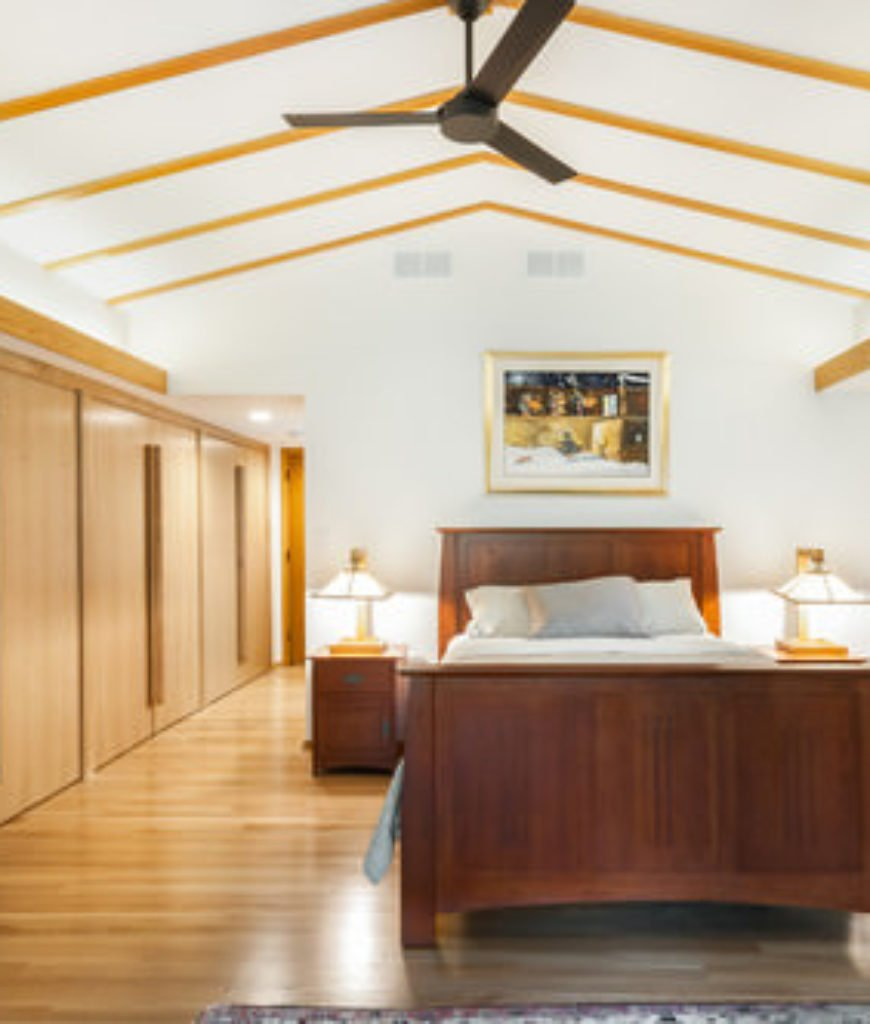 Large bedroom with high ceiling, open wood beams, white walls and wood flooring.