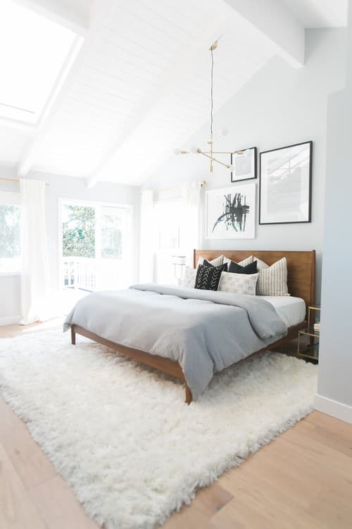 Refreshingly white midcentury bedroom accomplished with light wood flooring  and high wood ceiling.Photo by Lindye Galloway Interiors - Look for bedroom  ...