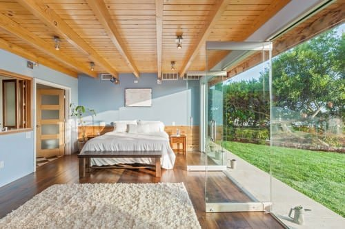 Mid-size master bedroom with beam ceiling, blue walls, hardwood flooring and full glazed walls with double glass doors.