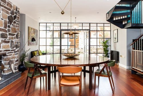 Open Concept Midcentury Dining Room With Pendant Lighting A Round Table And Stone