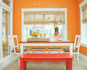 Contemporary orange dining room with white chairs and floor with rug.