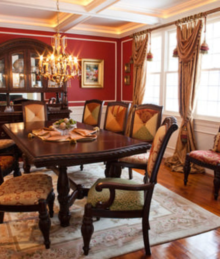 Eclectic red dining room with chandelier and hardwood floor with rug.