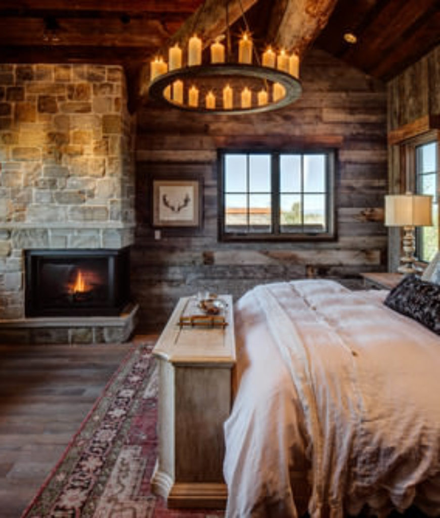 Mid-size mountain style master bedroom featuring farmer's stone and wood walls, candle chandelier and transitional wood flooring.