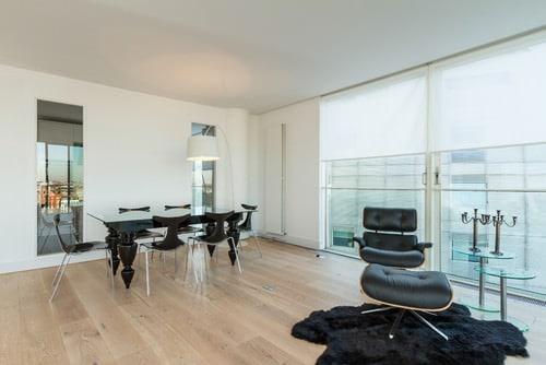 Scandinavian dining room with hardwood floor and black chair.