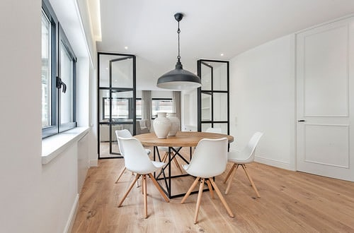 Scandinavian Dining Room With Pendant Light And Hardwood Floor.