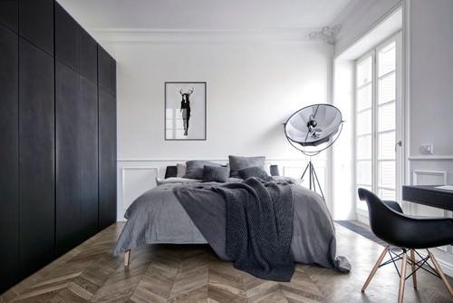 Scandinavian master bedroom with parquet floor and white walls.