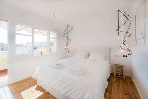 Scandinavian Master Bedroom With Hardwood Floor And Bed With White Covers.