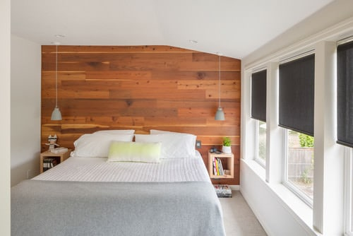 Scandinavian master bedroom with pendant light and wood panel wall.