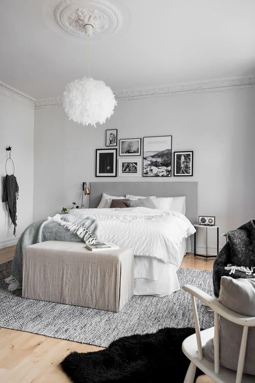 Scandinavian master bedroom with pendant light and hardwood floor with rug.
