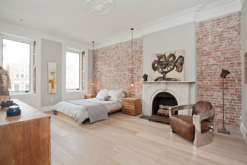 Scandinavian master bedroom with fireplace and pendant light.