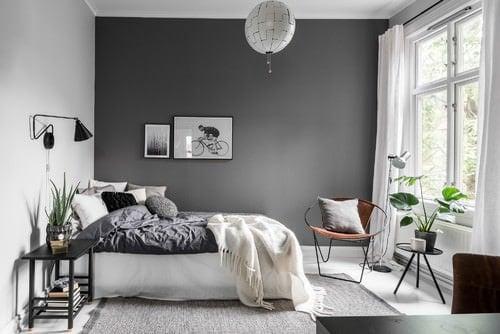 Scandinavian master bedroom with gray walls and floor with rug.