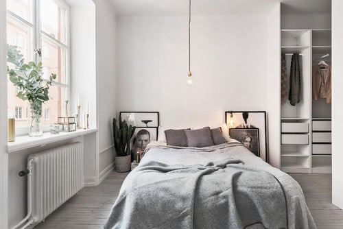 Scandinavian master bedroom with pendant light and white walls.