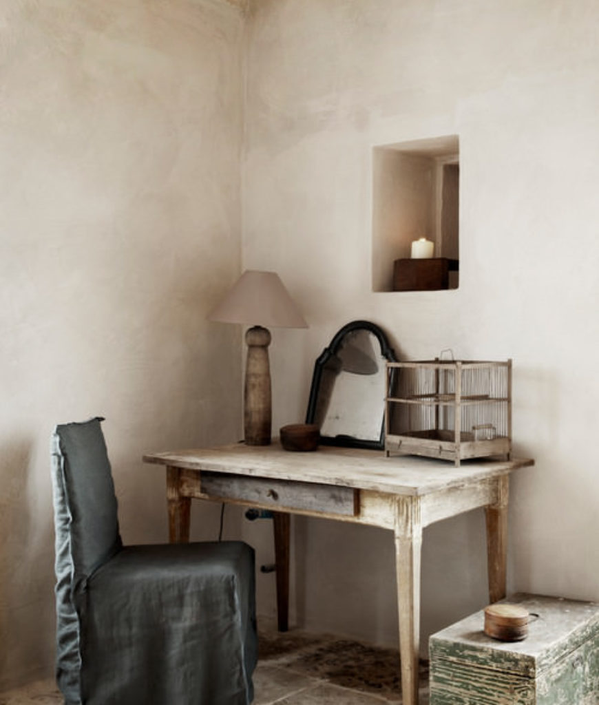 Shabby-chic home office with wooden table and table lamp.