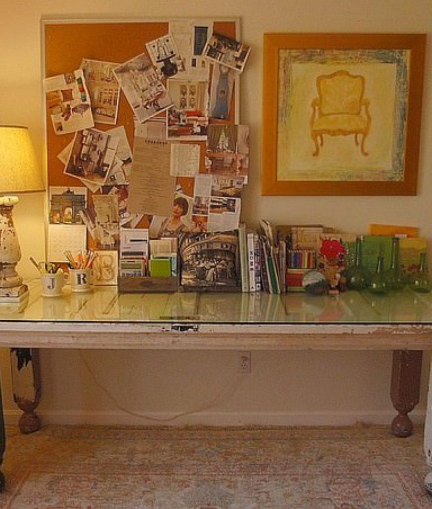 Shabby-chic home office with rectangular table, table lamp, and white walls.