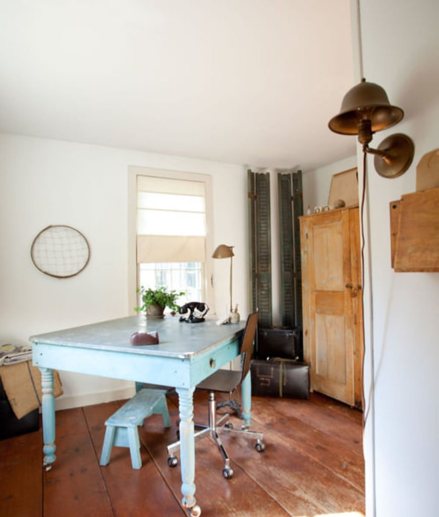 Shabby-chic home office with hardwood floor and wall light.
