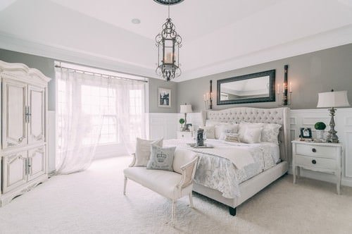 Scandinavian master bedroom with pendant light and floor with rug.