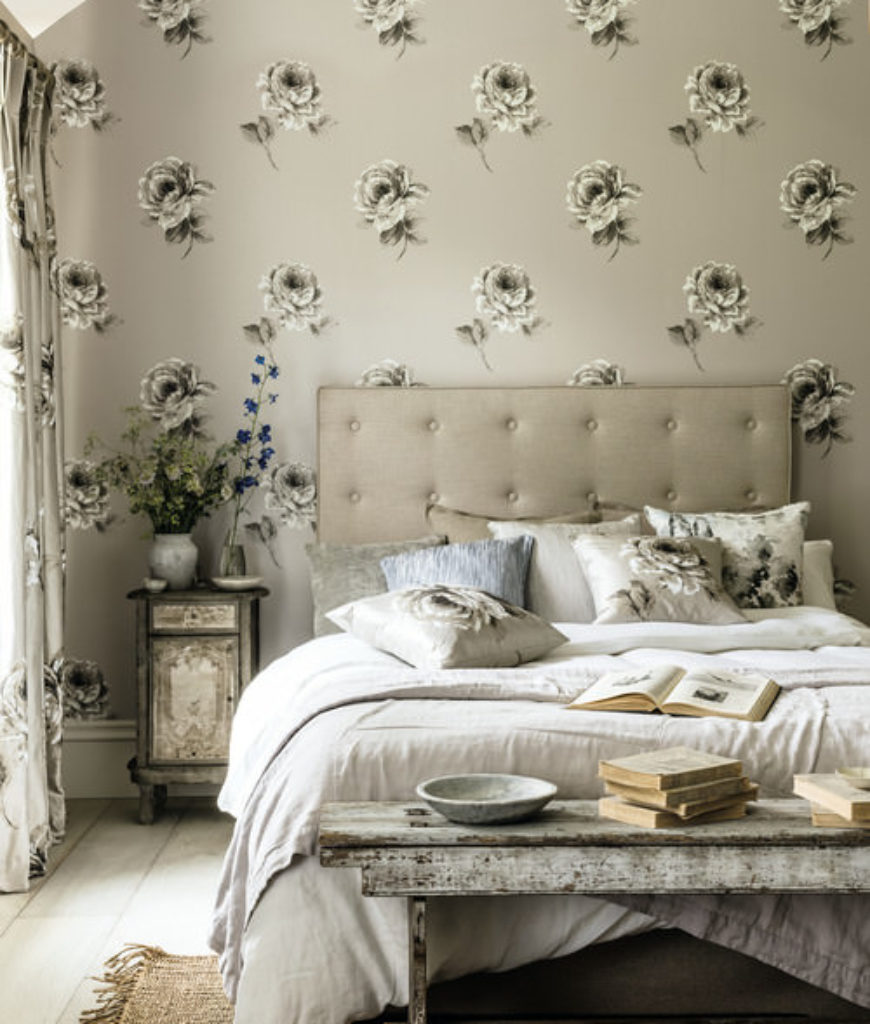 Shabby-chic master bedroom with wallpapered-wall and bed with white sheets.
