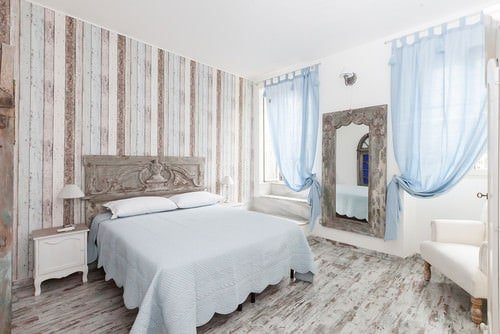 Shabby-chic primary bedroom with hardwood floor and bed with white sheets.