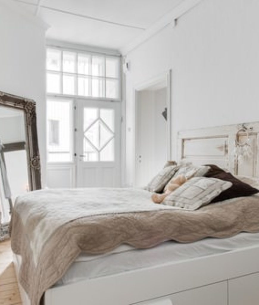 Shabby-chic master bedroom with full-size mirror and white walls.