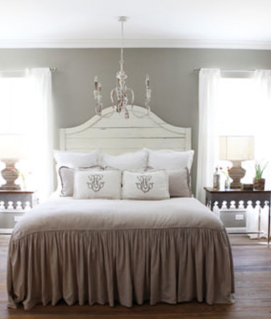 Shabby-chic master bedroom with chandelier and hardwood floor.