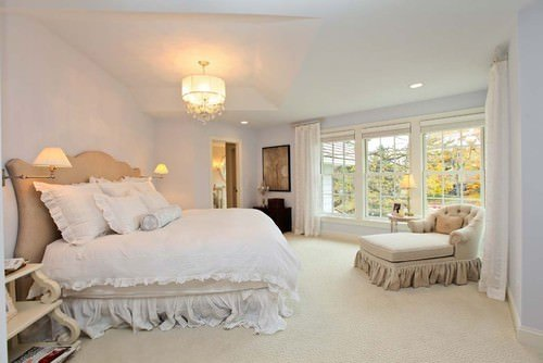 Shabby-chic master bedroom with pendant light and bed with white sheets.