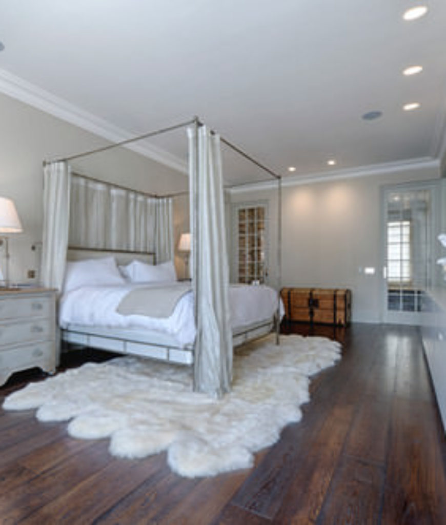 Shabby-chic master bedroom with hardwood floor and recessed lights.