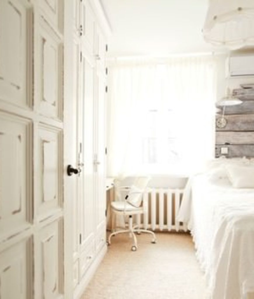 Shabby-chic master bedroom with white walls.
