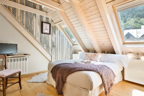 Shabby-chic master bedroom with vaulted ceiling and hardwood floor.