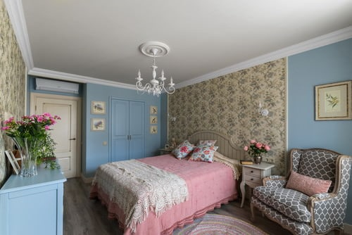Shabby-chic master bedroom with chandelier and bed with pink covers.