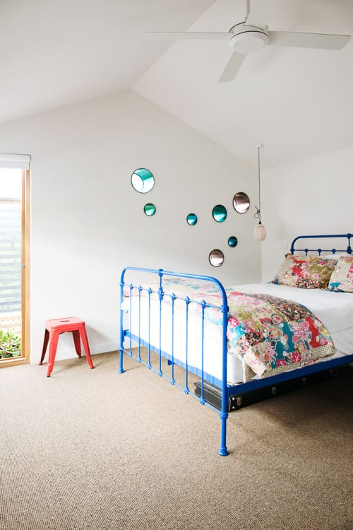 Shabby-chic master bedroom with stool and bed with blue frame.