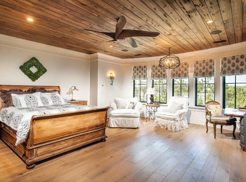This master bedroom boasts a wooden ceiling matching the hardwood flooring. The room also offers a cozy bed with a rustic frame. There's a sitting area on the side as well.