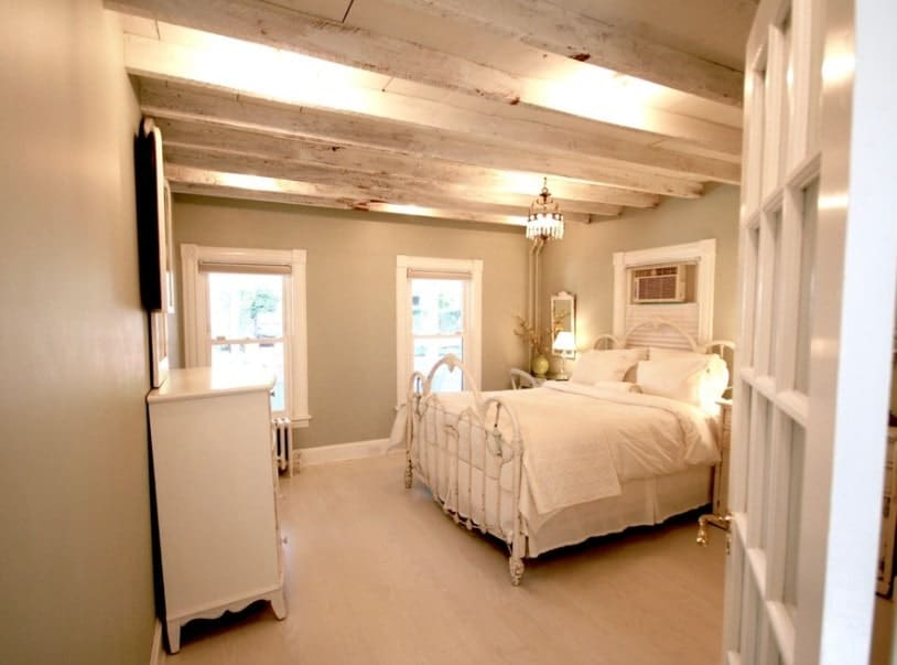 Master bedroom featuring carpet flooring and a ceiling with exposed beams. The room features a nice bed set as well.