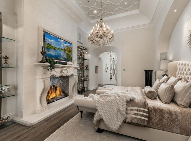 A Shabby Chic master bedroom boasting a luxurious bed, a stunning ceiling lighted by a fancy chandelier and a large classy fireplace with a widescreen TV on top of it.