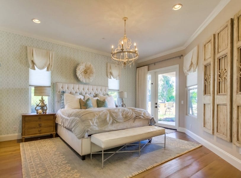 Primary bedroom boasting classy wall design and a gorgeous chandelier lighting up the place. The room also has hardwood floors topped by a stylish area rug.