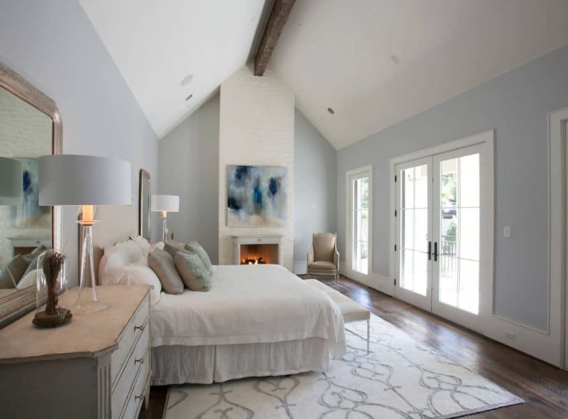 This primary bedroom offers a narrow vaulted ceiling with a single beam in the middle. The room also has light gray walls and hardwood floors topped by an area rug. The room offers a comfy bed and a fireplace on the side.
