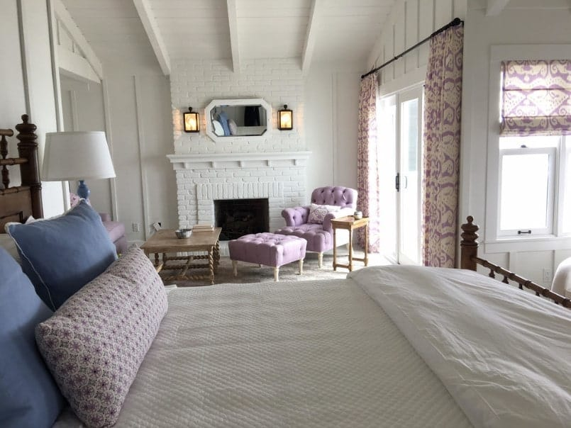 Master bedroom with a large cozy bed along with a comfy chair with a footrest near the brick fireplace.